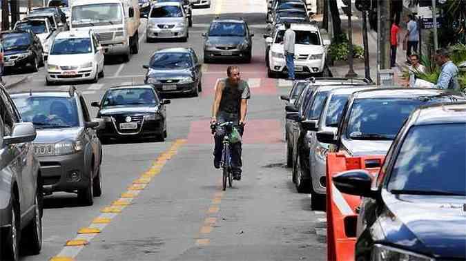 No quarteirão da Rua Fernandes Tourinho, entre ruas da Bahia e Espírito Santo, ciclista fica entre veículos estacionados e o trânsito intenso(foto: Gladyston Rodrigues/EM/D.A PRESS)