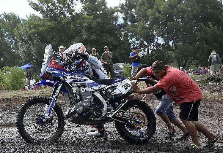 Francês Xavier  De Soultrait recebe ajuda de moradores para atravessar a lama na Argentina  - AFP PHOTO / FRANCK FIFE