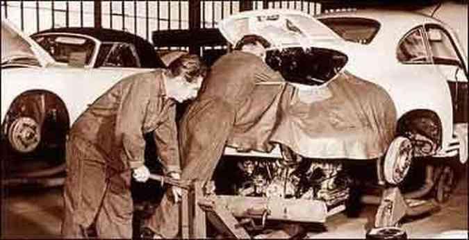 Nas instalações da fábrica da Porsche, em 1960, funcionários instalam o motor no 356
